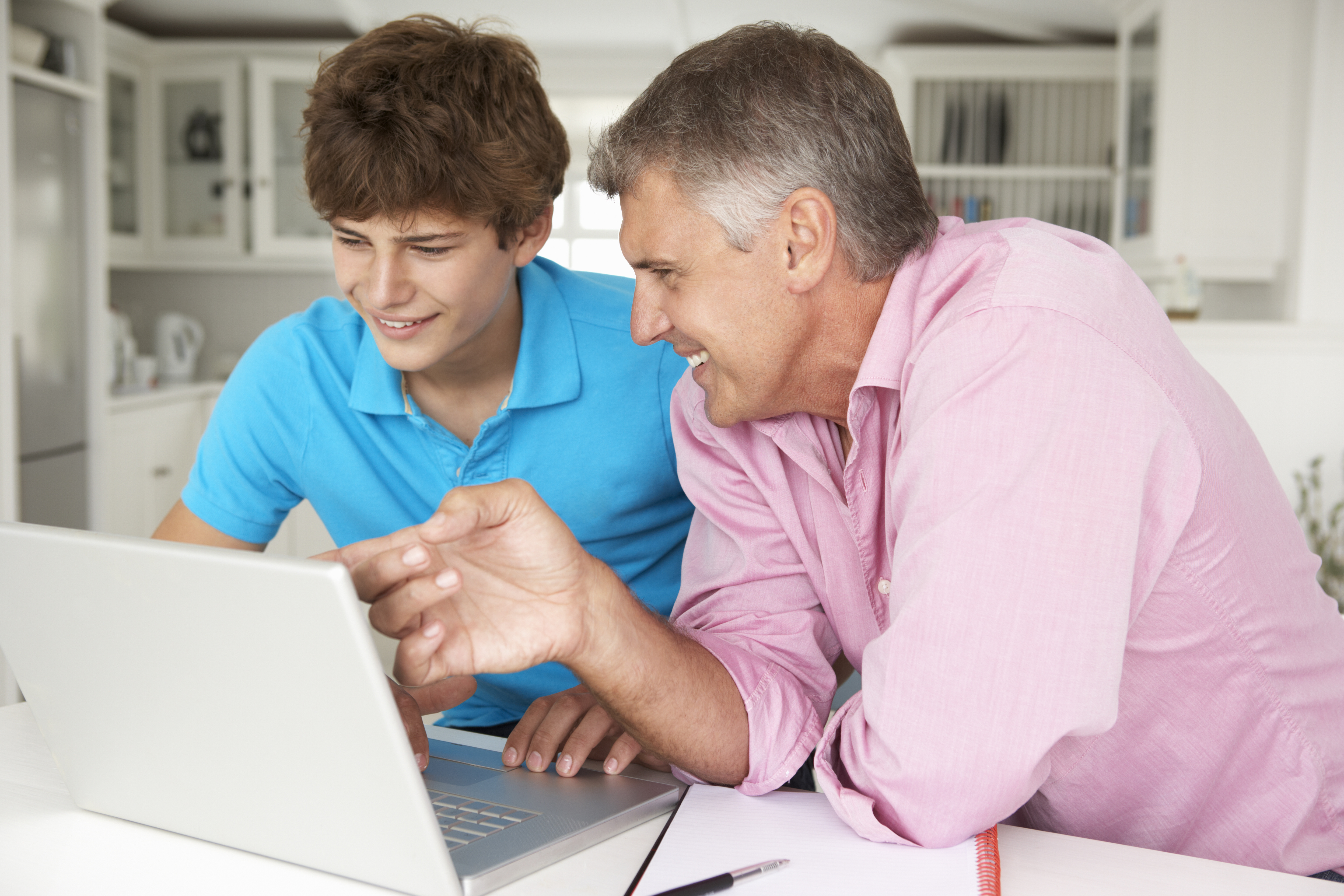 Father and teenage son using laptop
